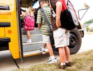 kids get on a school bus