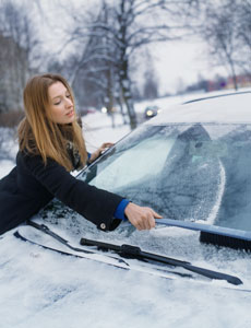 woman scraping ice off car