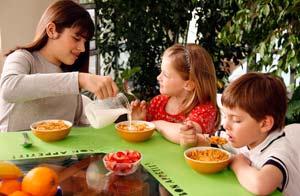 Joven comparte comida con niños/Glow images
