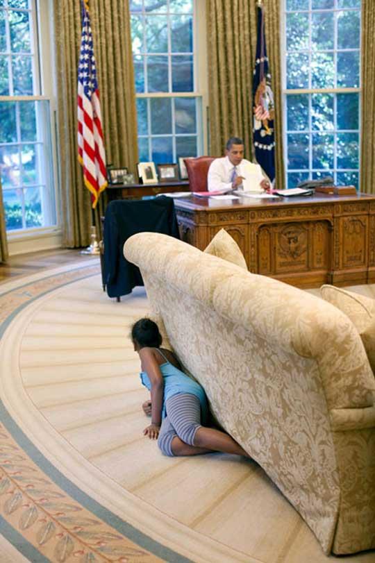 Mientras Barack Obama trabaja en el Salón Oval de la Casa Blanca, su hija Sasha -de 8 años- se esconde detrás de un sofá y espía, juguetona, el trabajo paterno / Foto: Pete Souza/Casa Blanca vía Getty Images