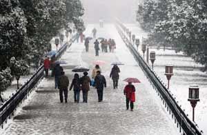 Visitantes caminan bajo la nieve en el Templo del Cielo de Pekín / EFE