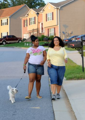 "In this July 11, 2011 photo, Stormy Bradley, right, and her daughter Maya, 14, walk their dog Bubbles in their neighborhood in Atlanta. Maya, who is 5'4"" tall and weighs about 200 lbs., is part of an anti-obesity ad campaign in Georgia. A provocative article in a prominent medical journal argues parents of extremely obese children should lose custody because they can't control their kids' weight. (AP Photo/Erik S. Lesser)"