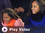President Barack Obama's daughters Sasha and Malia watch the inaugural parade in Washington, Tuesday, Jan. 20, 2009. (AP Photo/Jae Hong)