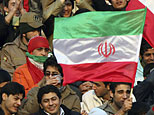 Iranian men hold their national flags during a soccer game. (AP photo/Hasan Sarbakhshian)
