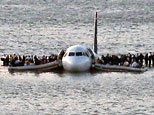 Passengers wait to be rescued on the wings of a US Airways Airbus 320 jetliner that safely ditched in the Hudson River in New York, after a flock of birds knocked out both its engines (AP Photo/Steven Day)
