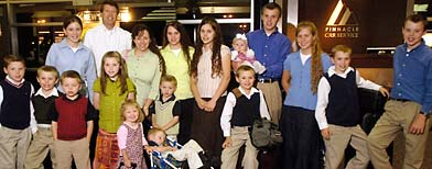 18 of the 19 members of the Duggar family pose for a photo at Northwest Arkansas Regional Airport in Highfil, Ark. on Friday, May 9, 2008. (AP)