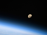 A gibbous moon is visible above Earth's atmosphere, photographed by an STS-128 crew member on the Space Shuttle Discovery, during flight day three activities in this NASA handout photo taken August 30, 2009. (REUTERS/NASA/Handout)
