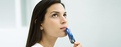 Woman holding credit card up to face, looking up (Getty Images)