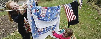 Carin Froehlich has help from her granddaughter Ava as they hang some laundry in the front yard of her residence in Perkasie, Pennsylvania, November 12, 2009. (REUTERS/Tim Shaffer)