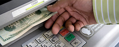 Person taking money from an ATM. (Getty Images)