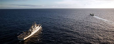 A Swedish warship, left, escorts a merchant ship, on Tuesday, May 11 ,2010, in the Indian Ocean. (AP Photo/Tim Freccia)