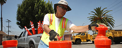 Ernest Beas, an employee of ICE Engineering, picks up traffic control posts after completing a speed bump construction project that was contracted out by the city of Maywood. (David McNew/Getty Images)