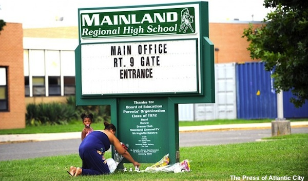 A memorial is left by the Mainland High School sign in memory of four football players who died in a car accident