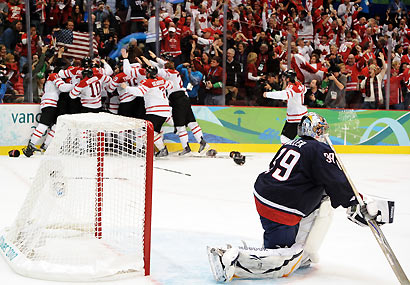 Ryan Miller (right) reacts as Canada celebrates Sidney Crosby's game-winning goal.
