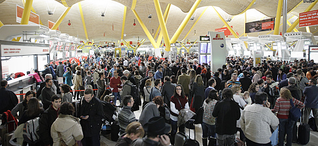 Passengers wait for news about their flights at the Barajas airport in Madrid.