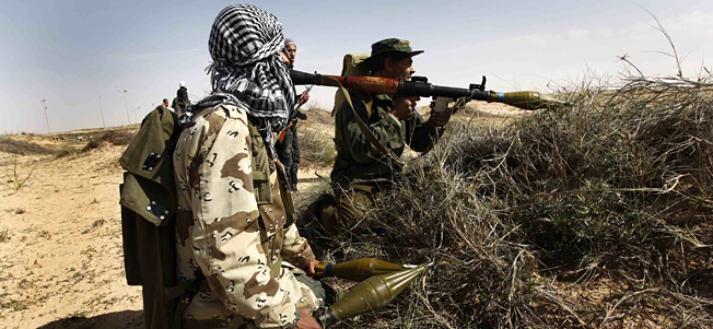 Libyan rebels with RPG launchers take their position during a battle against pro-Moaamar Gadhafi fighters, in the town of Brega, east of Libya, on Wednesday March 2, 2011