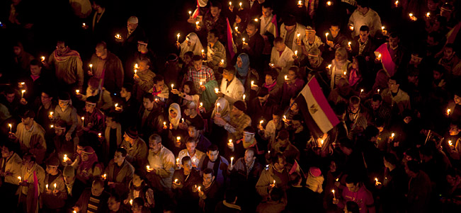 Anti-government protesters hold candles as they walk in Cairo, Egypt.