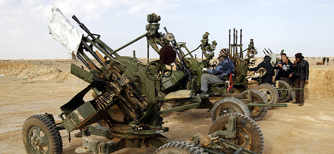 A rebel sits on an anti-aircraft gun on the outskirts of Ajdabiya on the road leading to Brega March 3, 2011
