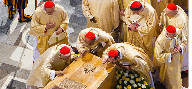 Cardinals kiss the casket of late Pope John Paul II, laid out in state at the Altar of the Confession inside St. Peter's Basilica