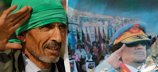 A Pro-Gadhafi supporter simulates the salute portrayed in a photograph of the Libyan Leader Moammar Gadhafi, as he and others stage a small rally in Sabratha, Libya, Monday, Feb. 28, 2011