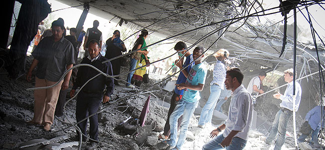 In this photo made on a government organized tour, supporters inspect damage at the Gadhafi family compound in a residential area of Tripoli, Libya, Sunday, May 1, 2011.