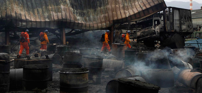 Members of a British search and rescue team search a smoldering industrial facility in Ofunato