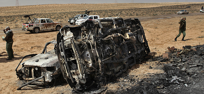 A Libyan rebel walks past the charred remains of the vehicles, belonging to the Libyan rebels, which were allegedly targeted in NATO coalition airstrikes overnight near Brega April 2, 2011