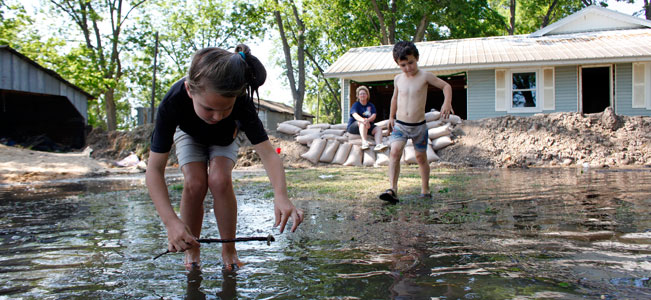 Chloe Creech picks up a crawfish from floodwaters while her brother Peyton Creech approaches as they play near the rising Yazoo River