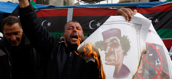 Palestinians in northern Gaza Strip burn a poster of Moammar Gadhafi in solidarity with the people of Libya