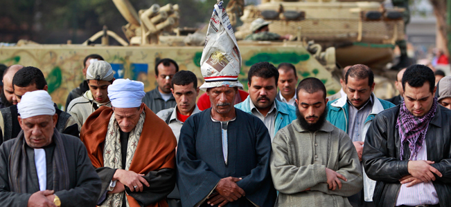 Anti-government protesters pray in front of an army tank in Cairo