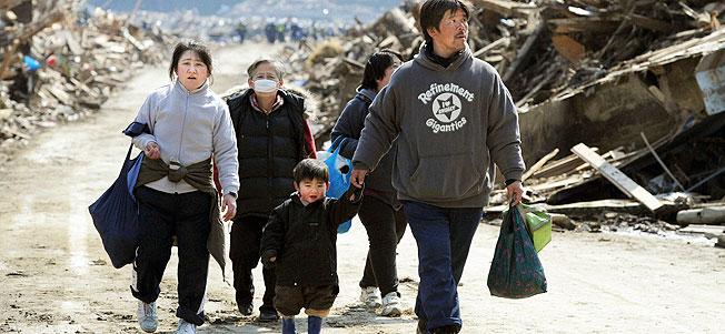 A family walks past buildings destroyed by a tsunami in Minamisanriku, Miyagi Prefecture, in northern Japan