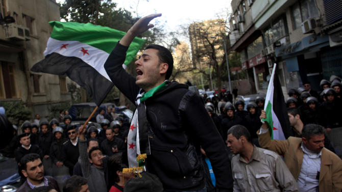 Egyptian and Syrian protesters chant slogans and hold Syrian revolutionary flags at a protest against Iran's President Mahmoud Ahmadinejad, during his visit to Egypt for the 12th summit of the Organization of Islamic Cooperation, in front of Iranian diplomatic representation office in Cairo, Egypt, Wednesday, Feb. 6, 2013. (AP Photo/Khalil Hamra)