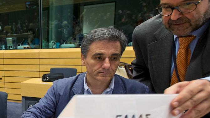 """Greek diplomat Brahos adjusts the sign on which is written """"Greece"""" in front of newly appointed Greek Finance Minister Tsakalotos at a euro zone finance ministers meeting on the situation in Greece in Brussels"""