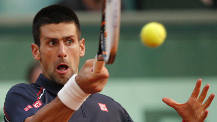 Serbia's Novak Djokovic returns the ball to France's Nicolas Devilder during their third round match in the French Open tennis tournament at the Roland Garros stadium in Paris, Friday, June 1, 2012. (AP Photo/Christophe Ena)