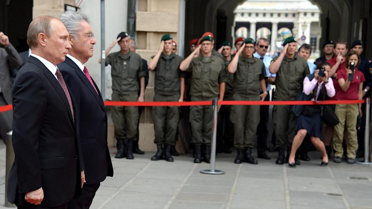 Russian President Vladimir Putin (C-L) and his Austrian counterpart Heinz Fischer (C-R) review a guard of honour at Hofburg Palace in Vienna on June 24, 2014