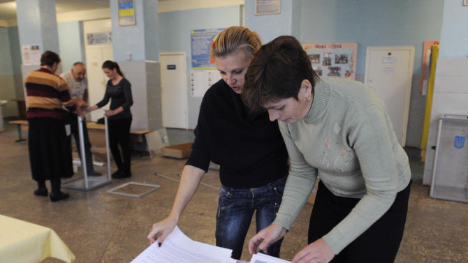 Workers prepare a polling station in the village of Bobryk, some 60 km (37 miles) north  of Kiev Ukraine, Saturday, Oct. 27, 2012.  Ukraine is scheduled to hold parliamentary elections on Oct. 28. (AP Photo/Sergei Chuzavkov)