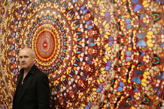"British artist Damien Hirst stands beside the 2006 piece ""I Am Become Death, Shatterer of Worlds"", butterflies and household gloss on canvas, during a media preview of the first substantial survey sho"