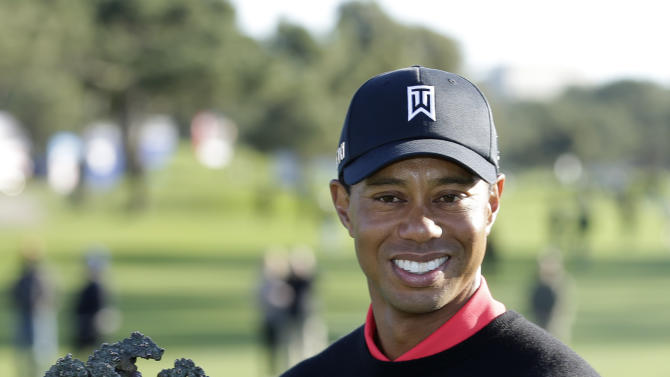 Tiger Woods holds up the trophy after winning the Farmers Insurance Open golf tournament at the Torrey Pines Golf Course Monday, Jan. 28, 2013, in San Diego. It is Wood's seventh victory in the event. (AP Photo/Gregory Bull)