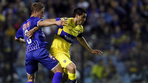 Boca Juniors' Juan Roman Riquelme (R) fights for the ball with Godoy Cruz's Facundo Castillon during their Argentine First Division soccer match in Buenos Aires