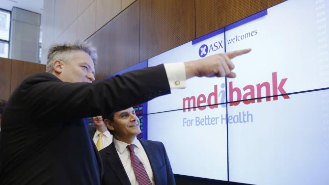 Australian Finance Minister Mathias Cormann watches the stock price of Medibank alongside the company's Managing Director George Savvides at the Australian Stock Exchange in Sydney