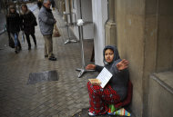 A woman gestures at the camera while she begs on the street in Pamplona, northern Spain, Friday, Jan. 27, 2012. The National Statistics Institute says Spain's unemployment figures has surpassed the 5 million mark, with the jobless rate shooting up from 21.5 percent to 22.8 percent in the fourth quarter. The new conservative Popular Party government pledges new labor reforms to try to halt further job destruction as Spain already has the highest unemployment rate in the 17-nation eurozone. (AP Photo/Alvaro Barrientos)