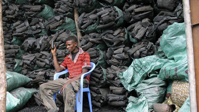 """In this photo of Tuesday Oct. 30, 2012 a Somali charcoal trader listen to his radio as he waits for customers at his charcoal store in Mogadishu, Somalia. Thousands of sacks of dark charcoal sit atop one another in Somalia's southern port city of Kismayo, an industry once worth some $25 million dollar a year to the al-Qaida-linked insurgents who controlled the region.  The good news sitting in the idle pile of sacks is that al-Shabab militants can no longer fund their insurgency through the illegal export of the charcoal. Kenyan troops late last month invaded Kismayo and forced out the insurgents, putting a halt to the export of charcoal, a trade the U.N. banned earlier this year in an effort to cut militant profits. The loss of the charcoal trade """"will cut a major source of revenue and thus will have a detrimental effect on their operational capacity to carry out large scale attacks,"""" Mohamed Sheikh Abdi, a Somali political analyst, said of al-Shabab.  But the flip side to the charcoal problem is that residents who made their living from the trade no longer are making money, a potentially tricky issue for the Kenyan troops who now control the region. (AP Photo/Farah Abdi Warsameh)"""