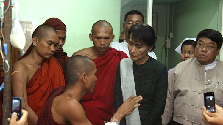 FILE - In this Thursday, Nov 29, 2012 file photo, opposition leader Aung San Suu Kyi, second right, listens to a Buddhist monk who suffered from burn injuries when security forces cracked down protesters camping at a military-backed copper mine, during her visit to a hospital in Monywa, northwestern Myanmar. For Suu Kyi the democracy activist, the 25-year struggle against Myanmar's former army rulers was a largely black-and-white affair - a clear fight for freedom against one of the world's most oppressive regimes. But Suu Kyi the elected lawmaker is finding it a lot more difficult to pick her battles, and she's a lot more pragmatic when she does. (AP Photo/File)