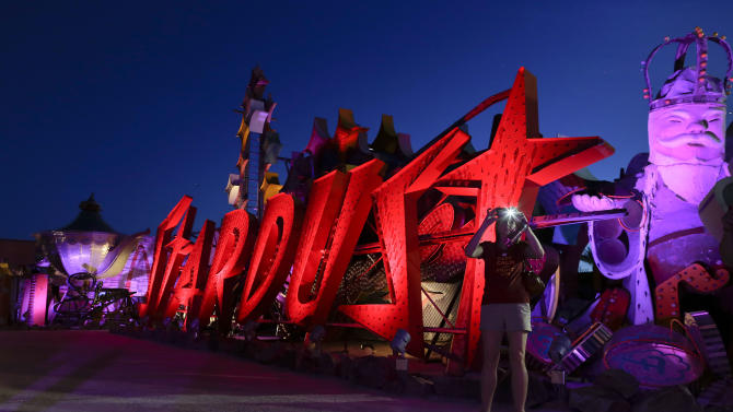 A tourist takes a photo at the Neon Museum in Las Vegas on Friday, May 24, 2013. For the past six months, visitors have had to squint up at the hulking metal forms through the desert sun. On Friday, the museum unveiled nighttime hours. (AP Photo/Julie Jacobson)