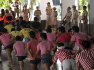 "Thai prison officials, background, watch as inmates do the stretching before performing ""Gangnam Style"" dance during the dancing competition at a prison in Bangkok, Thailand Tuesday, Nov. 27, 2012. The event was held to encourage inmates to do more exercise and coincide with the concert of South Korean rapper PSY's ""Gangnam Style"" to be held in Bangkok on Wednesday, Nov. 28. (AP Photo/Apichart Weerawong)"