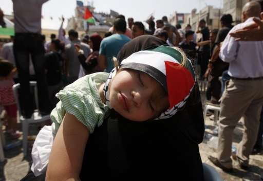 Palestinian woman holds a sleeping girl during a rally in the West Bank city of Ramallah