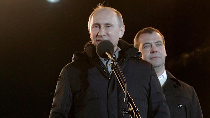 Russian Prime Minister and presidential candidate Vladimir Putin, left, flanked by President Dmitry Medvedev, addresses a massive rally of his supporters at Manezh square outside Kremlin, in Moscow, Russia, Sunday, March 4, 2012. Vladimir Putin has claimed victory in Russia's presidential election, which the opposition and independent observers say has been marred by widespread violations. Putin made the claim at a rally of tens of thousands of his supporters just outside the Kremlin, thanking his supporters for helping foil foreign plots aimed to weaken the country. (AP Photo/Ivan Sekretarev)
