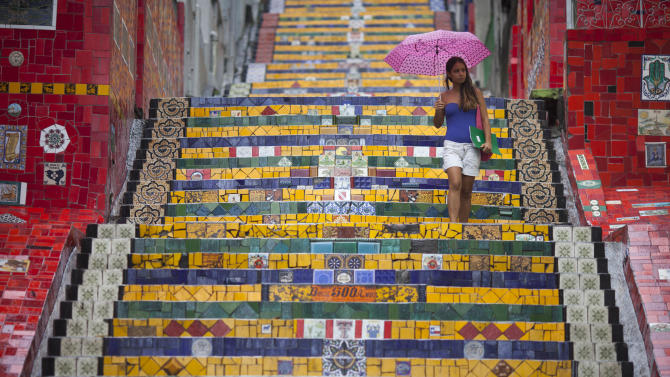 """A woman descends a stairway that was decorated by Chilean artist Jorge Selaron, which he titled the """"Selaron Stairway"""" in Rio de Janeiro, Brazil, Thursday, Jan. 10, 2013. Selaron, an eccentric Chilean artist and longtime Rio resident who created a massive, colorful tile stairway in the bohemian Lapa district that's popular with tourists, was found dead on the stairway on Thursday. He was 54. Authorities are investigating the cause of death. (AP Photo/Felipe Dana)"""
