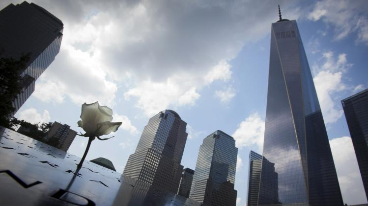 A flower is pictured at the 9/11 Memorial with the One World Trade Center in the background, in New York