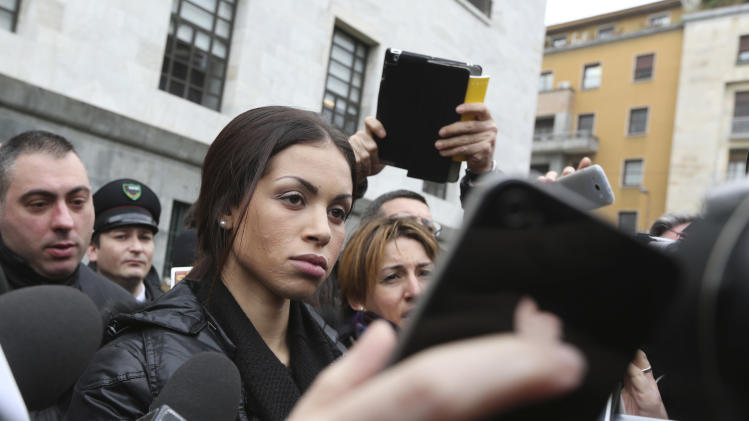 Karima el-Mahroug, also known as Ruby, center, a Moroccan woman at the center of ex-Premier Silvio Berlusconi's sex-for-hire trial, is surrounded by reporters outside Milan's court house, Italy, Thursday, April 4, 2013. The Moroccan woman at the center of ex-Premier Silvio Berlusconi's sex-for-hire trial has denounced what she says is psychological warfare being waged against her by Italian prosecutors. Ruby, read out a lengthy statement Thursday to a gaggle of reporters in front of Milan's courthouse denying she was a prostitute and insisting that prosecutors hear her side of the story. (AP Photo/Luca Bruno)